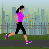 Dziewczyna biega w sportswear na tle miastowy krajobraz przy zmierzchem z hełmofonami Fotografia Stock