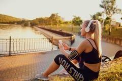 Dziewczyna biegacz słucha muzyka w parku Zdjęcia Stock
