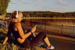 Dziewczyna biegacz słucha muzyka w parku Zdjęcia Royalty Free