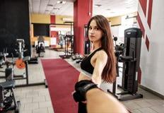 Dziewczyna bierze jego boyfiend rękę w gym obrazy royalty free