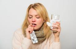 Dziewczyna bierze medycyna napoju wodę Migreny i zimna remedia Kobieta kudłacący włosiany szalika chwyta pastylek bąbel Grypa I z fotografia royalty free