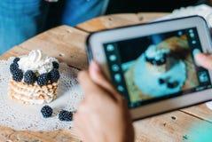 Dziewczyna bierze obrazki tort na pastylce zdjęcie stock
