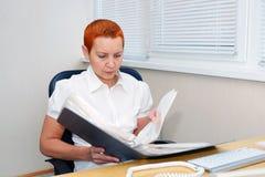 Dziewczyna biurowy kierownik patrzeje dokumenty skoncentrowany fotografia royalty free