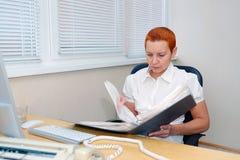 Dziewczyna biurowy kierownik patrzeje dokumenty skoncentrowany obraz stock