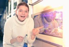 Dziewczyna blisko dużego akwarium wskazuje ciekawy model aquar Obraz Stock