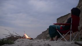 Dziewczyna blisko ogniska na plaży zdjęcie wideo