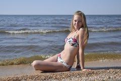 Dziewczyna blondynka w bikini obsiadaniu na plaży w piasku Piękna młoda kobieta w kolorowym bikini na dennym tle Fotografia Royalty Free