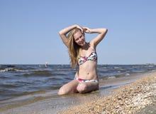 Dziewczyna blondynka w bikini obsiadaniu na plaży w piasku Piękna młoda kobieta w kolorowym bikini na dennym tle Zdjęcie Stock