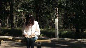 Dziewczyna był zmęczona czytać podręcznika i rzucał ona zbiory wideo