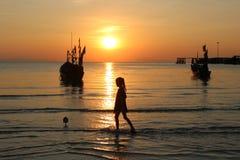 Dziewczyna chodził na plaży z zmierzchem i łodzią rybacką Zdjęcia Royalty Free