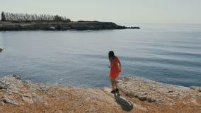 Dziewczyna chodzi blisko urwiska nad morzem zbiory