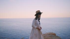 Dziewczyna chodzi na krawędzi falezy obok oceanu zbiory wideo