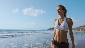 Dziewczyna chodzi plażę w wodzie i zdjęcie wideo