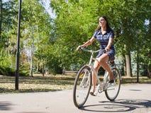 Dziewczyna chodzi w dół ulicę na jej rowerze fotografia stock