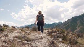 Dziewczyna chodzi wzdłuż ścieżki w skalistym terenie Młoda kobieta turysta z plecakiem zdjęcie wideo