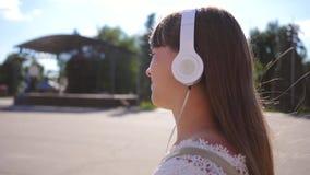 Dziewczyna chodzi wzdłuż miasto ulicy z hełmofonami, słucha muzyka i ono uśmiecha się dziewczyna w białej sukni z długie włosy zbiory wideo