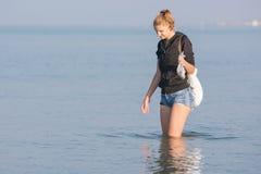 Dziewczyna chodzi wzdłuż plaży i zbiera skorupy w morzu w ranku wcześnie Zdjęcie Stock