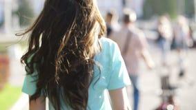 Dziewczyna chodzi wzdłuż ulicy, jej włosy lata zbiory wideo