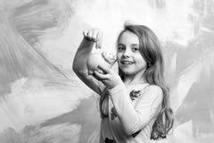 Dziewczyna chwyta moneybox lub prosiątko bank dla savings Zdjęcia Stock