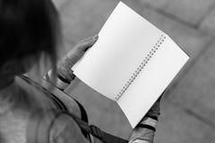 Dziewczyna chwyty otwierają notatnika, odgórny widok, czarny i biały fotografia Obrazy Royalty Free