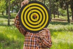 Dziewczyna chwyty w ręki dartboard z strzała w centrum celu outside w parku Obraz Stock