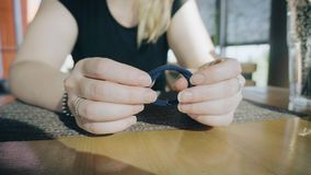 Dziewczyna ciągnie wewnątrz ręki gumowy zespół dla włosy Siedzi przy stołem w kawiarni i czekać na rozkaz zbiory