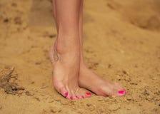 Dziewczyna cieki z jaskrawym pedicure'em i tatuażu stać bosy na żółtym piasku Obrazy Royalty Free