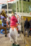 Dziewczyna cieszy się carousel przejażdżkę w parku rozrywki, Obrazy Royalty Free