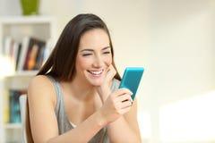 Dziewczyna cieszy się dopatrywanie środków zawartość na mądrze telefonie Zdjęcia Stock