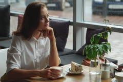Dziewczyna cieszy się fragrant kawy i cukierki tortowego obsiadanie w kawiarni Biznesowa kobieta odpoczywa podczas przerwy Obrazy Stock