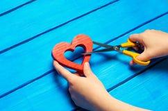 dziewczyna ciie serce z nożycami pojęcie łamań powiązania, bełty i rozwód, Zdrada othere Błękitny backgroun fotografia stock