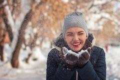 Dziewczyna cios przy śniegiem Zdjęcia Stock