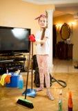 Dziewczyna czyści up żyć pokój z próżniowym cleaner, mopem i miarką, Fotografia Stock