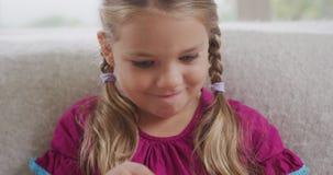 Dziewczyna czyta książkę na kanapie w żywym pokoju przy wygodnym domem 4k zbiory wideo