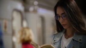 Dziewczyna czyta książkę na tle przelotny metro, zwolnione tempo zbiory
