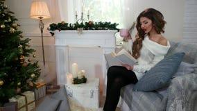 Dziewczyna czyta książkę, pijący herbaty, marzy, młoda dziewczyna relaksuje kobiety jest ubranym ciepłego, podczas gdy siedzący n zbiory wideo