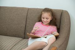 Dziewczyna czyta książkę podczas gdy kłamający na kanapie obrazy stock