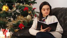Dziewczyna czyta książkę podczas gdy siedzący blisko choinki zdjęcie wideo