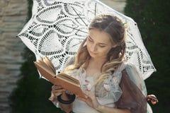 Dziewczyna czyta książkę podczas gdy stojący pod parasolem obraz stock