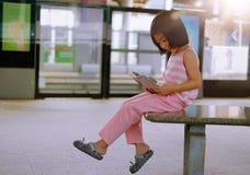 Dziewczyna czyta książkę przy dworcem Zdjęcia Royalty Free