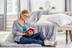 Dziewczyna czyta książkę w domu fotografia stock
