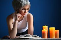 Dziewczyna czyta książkę w srebnej peruce i białym singlet z bliska niebieska tła Obrazy Royalty Free