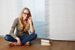 Dziewczyna czyta książkowego obsiadanie na podłoga fotografia stock