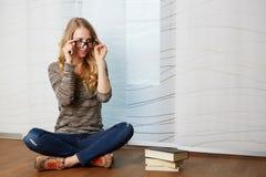 Dziewczyna czyta książkowego obsiadanie na podłoga obraz royalty free