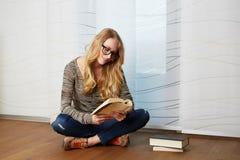 Dziewczyna czyta książkowego obsiadanie na podłoga obrazy royalty free