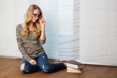 Dziewczyna czyta książkowego obsiadanie na podłoga fotografia royalty free