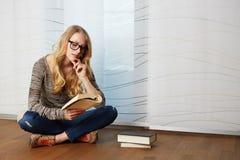 Dziewczyna czyta książkowego obsiadanie na podłoga zdjęcia royalty free