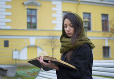 Dziewczyna czyta książkowego outside Fotografia Stock