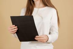 Dziewczyna czyta A4 pustą czarną ulotki broszurki broszurę Ulotek pres Fotografia Stock