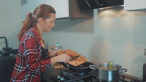 Dziewczyna dłoniaka marchewki w niecce kobieta kucharzi w kuchni robi prażakowi w domu Portret młodej kobiety sumująca marchewka zdjęcie wideo